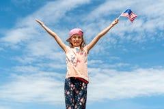 Liten flicka som rymmer en amerikanska flaggan Royaltyfri Fotografi