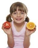 Liten flicka som rymmer en half tomat och en half orang Fotografering för Bildbyråer