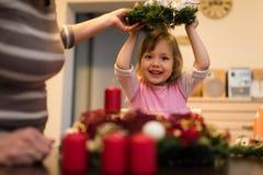 Liten flicka som rymmer en julkrans ovanför hennes huvud royaltyfri fotografi