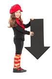 Liten flicka som rymmer en pil som ner pekar Arkivbild