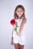 Liten flicka som rymmer en röd blomma som erbjuder för dig Arkivbild
