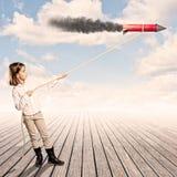 Liten flicka som rymmer en raket med ett rep arkivfoton