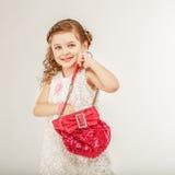 Liten flicka som rymmer en rosa handväska Arkivfoton