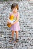Liten flicka som rymmer en släntra av bröd Royaltyfri Foto