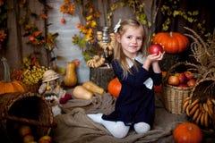 Liten flicka som rymmer ett äpple i en äppleinre royaltyfri bild