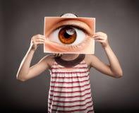 Liten flicka som rymmer ett öga arkivbilder