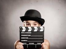Liten flicka som rymmer ett filmclapperbräde royaltyfria foton