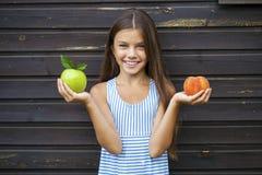 Liten flicka som rymmer ett grönt äpple och en persika royaltyfri fotografi
