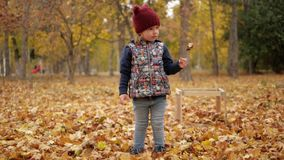 Liten flicka som rymmer ett gult blad i hennes händer stock video