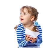 Liten flicka som rymmer ett pappers- fartyg på en vit backgr Royaltyfri Bild
