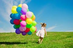 Liten flicka som rymmer färgrika ballonger. Barn som spelar på en gräsplan arkivbilder