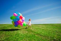 Liten flicka som rymmer färgrika ballonger. Barn som spelar på en gräsplan