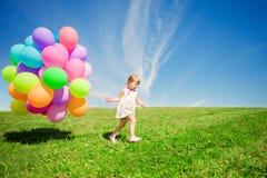 Liten flicka som rymmer färgrika ballonger. Barn som spelar på en gräsplan Royaltyfri Foto