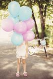 Liten flicka som rymmer färgrika ballonger i rosa färger och blått Cykel i bakgrunden - födelsedaggåva Födelsedagflicka - 4 åriga royaltyfri fotografi