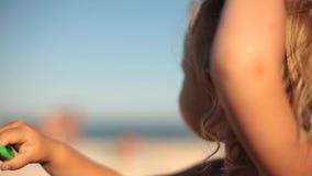 Liten flicka som rymmer kabel av en flygadrake på stranden i sommar arkivfilmer