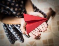 Liten flicka som rymmer röd origami för ett flygplanpapper Arkivfoton