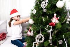 Liten flicka som sätter christmassträdprydnader arkivfoto