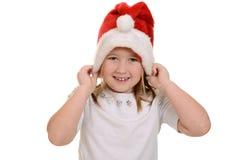 Liten flicka som sätter på den santa hatten Arkivbild