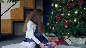 Liten flicka som söker efter gåvor under julgranen arkivfilmer