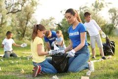 Liten flicka som samlar avfall med volontären arkivfoto