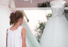 Liten flicka som ser bröllopsklänningar royaltyfri bild