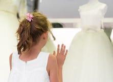 Liten flicka som ser bröllopsklänningar royaltyfri fotografi