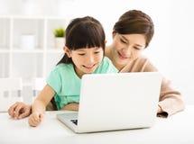 Liten flicka som ser bärbara datorn med hennes moder Arkivbilder