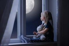 Liten flicka som ser den stjärnklara himlen och månen Arkivfoto