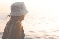 Liten flicka som ser havet på solnedgången arkivbilder