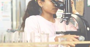 Liten flicka som ser in i ett mikroskop 4k lager videofilmer
