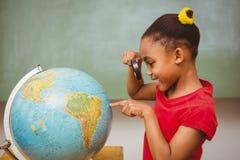 Liten flicka som ser jordklotet till och med förstoringsglaset Arkivfoton