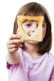 Liten flicka som ser till och med bröd Arkivfoto