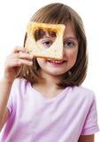 Liten flicka som ser till och med ett bröd Royaltyfria Bilder