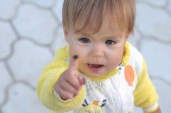 Liten flicka som ser upp på fingret Arkivbild