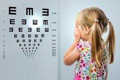 Liten flicka som ser visionprovdiagrammet royaltyfria foton