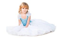 Liten flicka som sitter i ursnygg blå kappa på white Arkivbild