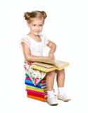Liten flicka som sitter på bunt av böcker Fotografering för Bildbyråer