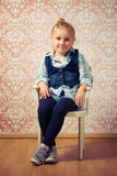 Liten flicka som sitter på en stol Royaltyfri Bild