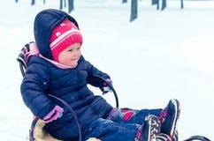 Liten flicka som sitter på hennes släde i vinterdag royaltyfria foton