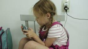 Liten flicka, som sitter på stolen, försök till att spela en lek med hennes smartphone Barn som använder mobiltelefonen arkivfilmer