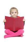 Liten flicka som sitter på golvet som läser boken Fotografering för Bildbyråer