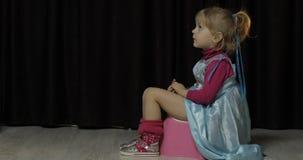 Liten flicka som sitter p? pottan och den h?llande ?gonen p? TV:N arkivbild