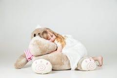 Liten flicka som sitts med den keliga leksaken och leende Royaltyfri Foto
