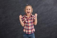 Liten flicka som skriker på grå bakgrund arkivbilder