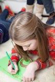 Liten flicka som skrivar ett brev från Santa Claus Fotografering för Bildbyråer