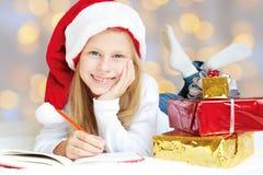 Liten flicka som skrivar ett brev till Santa Claus Royaltyfria Bilder