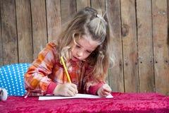 Liten flicka som skriver en bokstav Arkivfoton