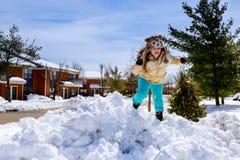 Liten flicka som skyfflar snö på hem- drevväg Härlig snöig trädgård eller främre gård Barn med skyffeln som utomhus spelar i vint royaltyfri foto