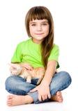 Liten flicka som slår en kattunge bakgrund isolerad white Arkivbild