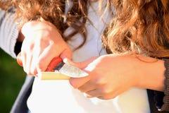 Liten flicka som snider en träpinne Fotografering för Bildbyråer